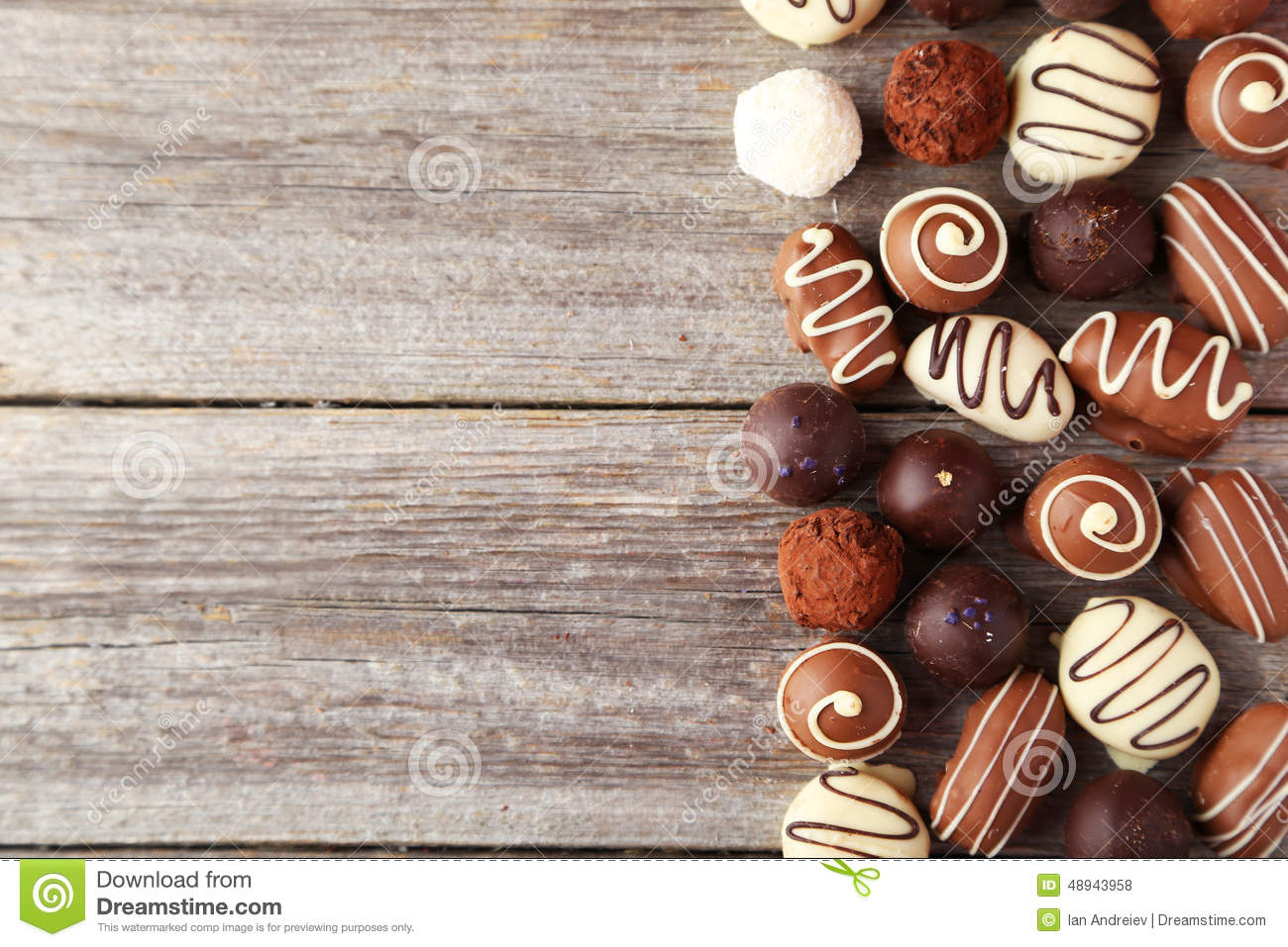 Chocolates on plate on a grey wooden background