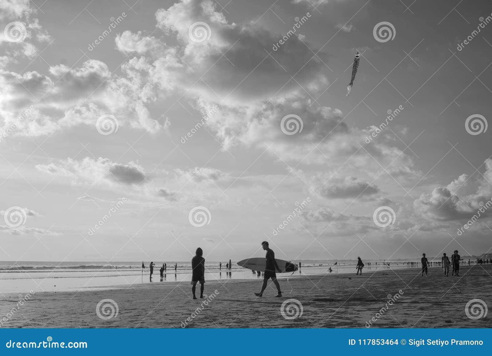 Chodzący z chwyta surferboard przy Kuta plażą, Indonezja w zmierzchu czasie