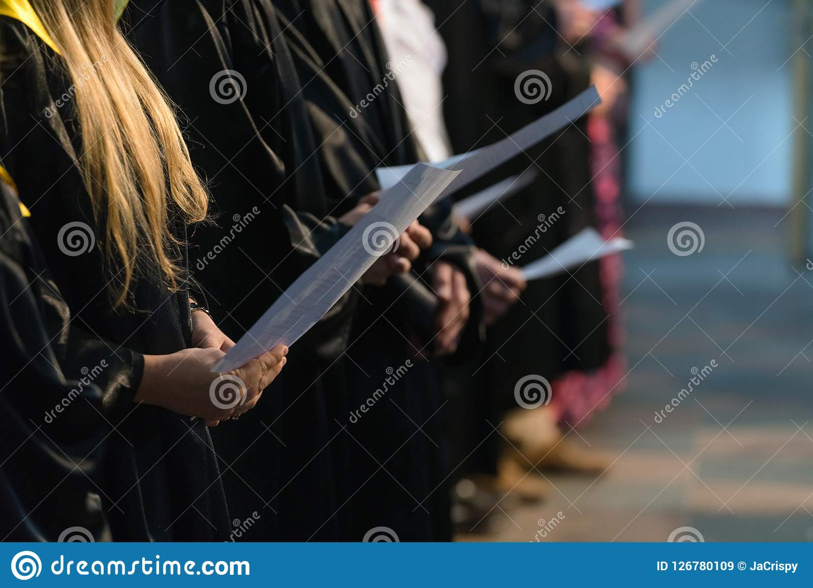 Choir singers holding musical score and singing on student graduation day in university, college diploma commencement