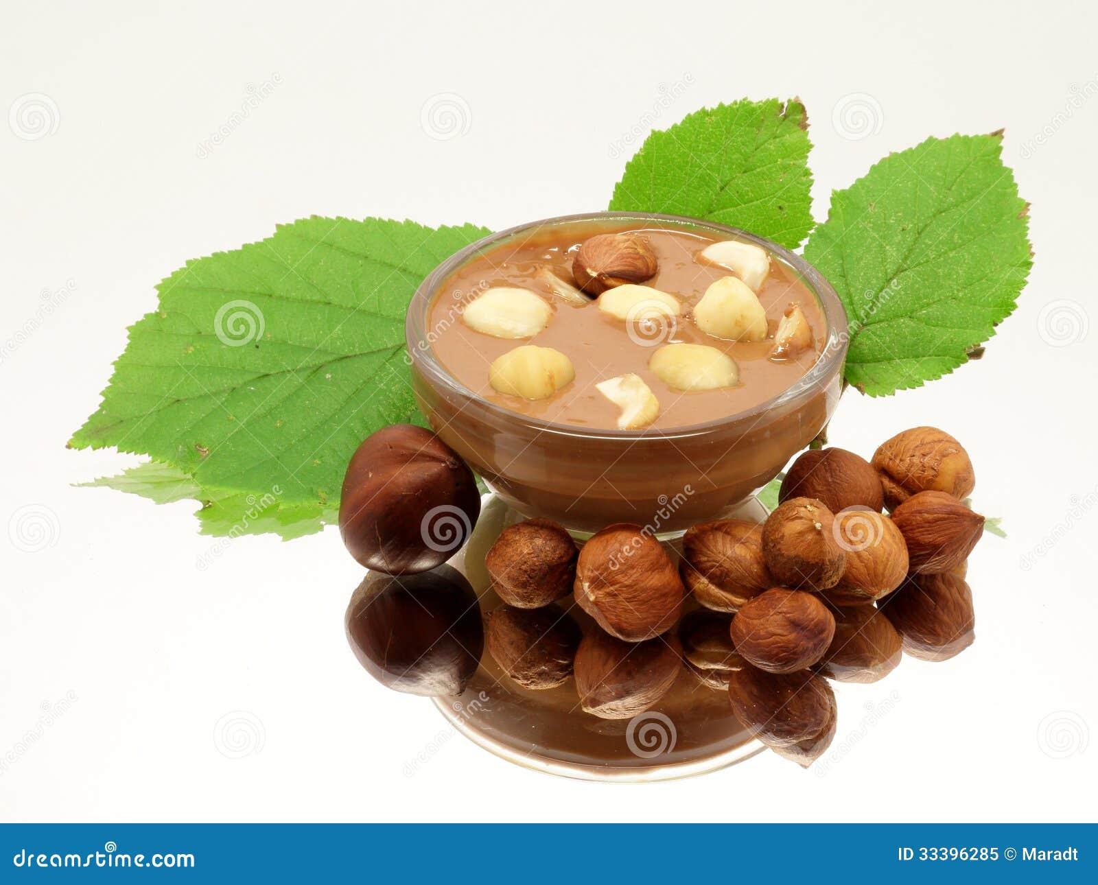 Choklad i den glass bunken med hasselnötter och blad
