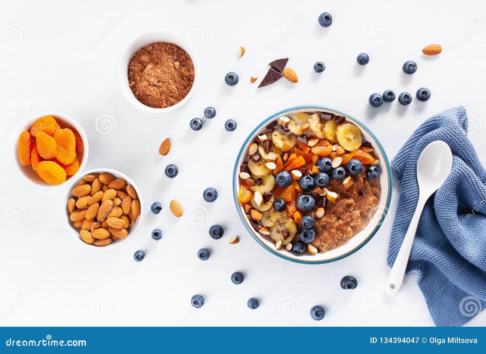 Chokladhavremjölhavregröt med blåbäret, muttrar, banan, torkad aprikos för bästa sikt för sund frukost