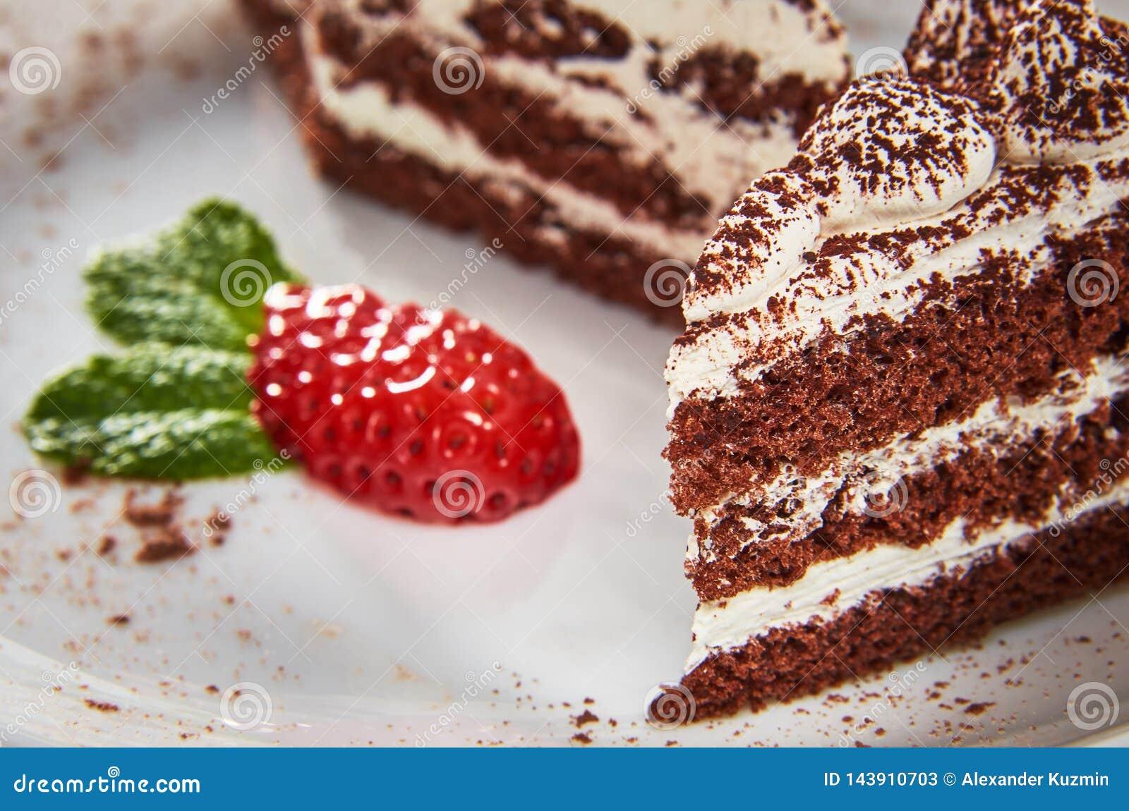 Chokladkaka på en vit platta med jordgubbar och mintkaramellen
