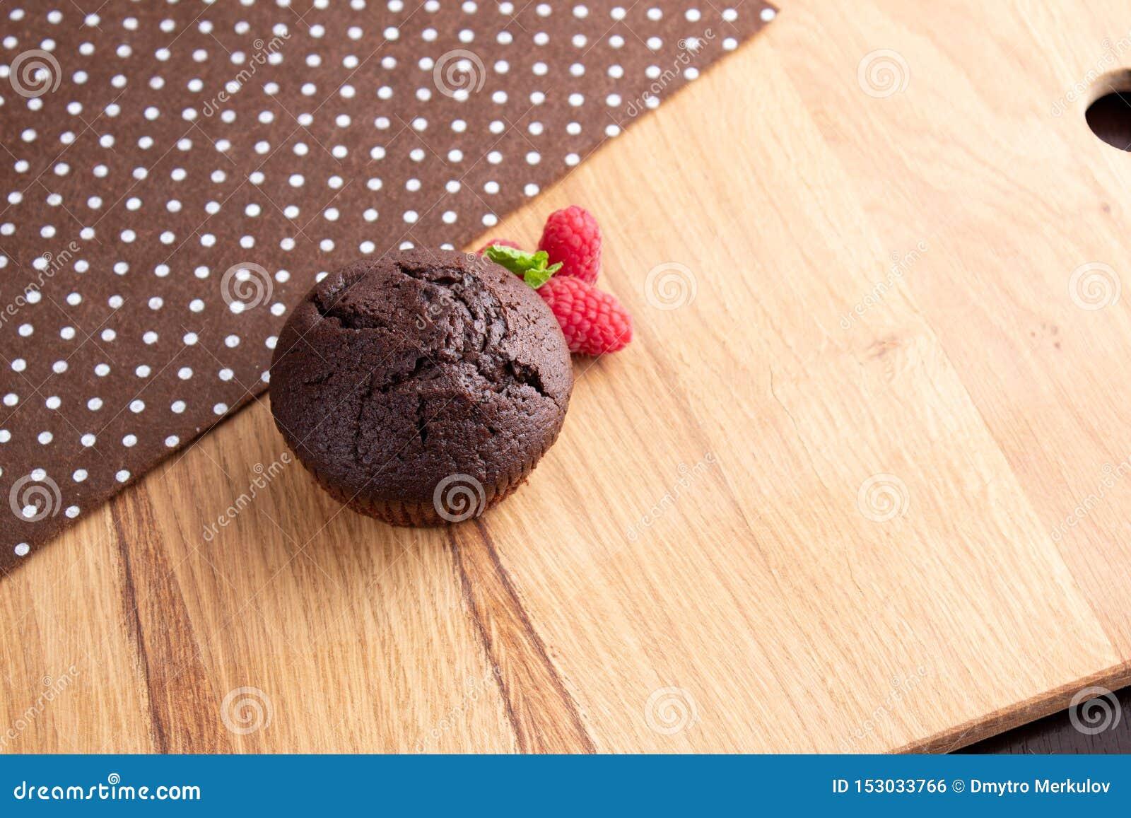 Chokladmuffin med hallonbär på en ljus trätabell