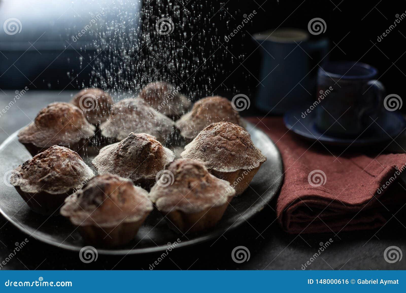 Cholate Mufins com uma nuvem da farinha no backgroundGROUND preto