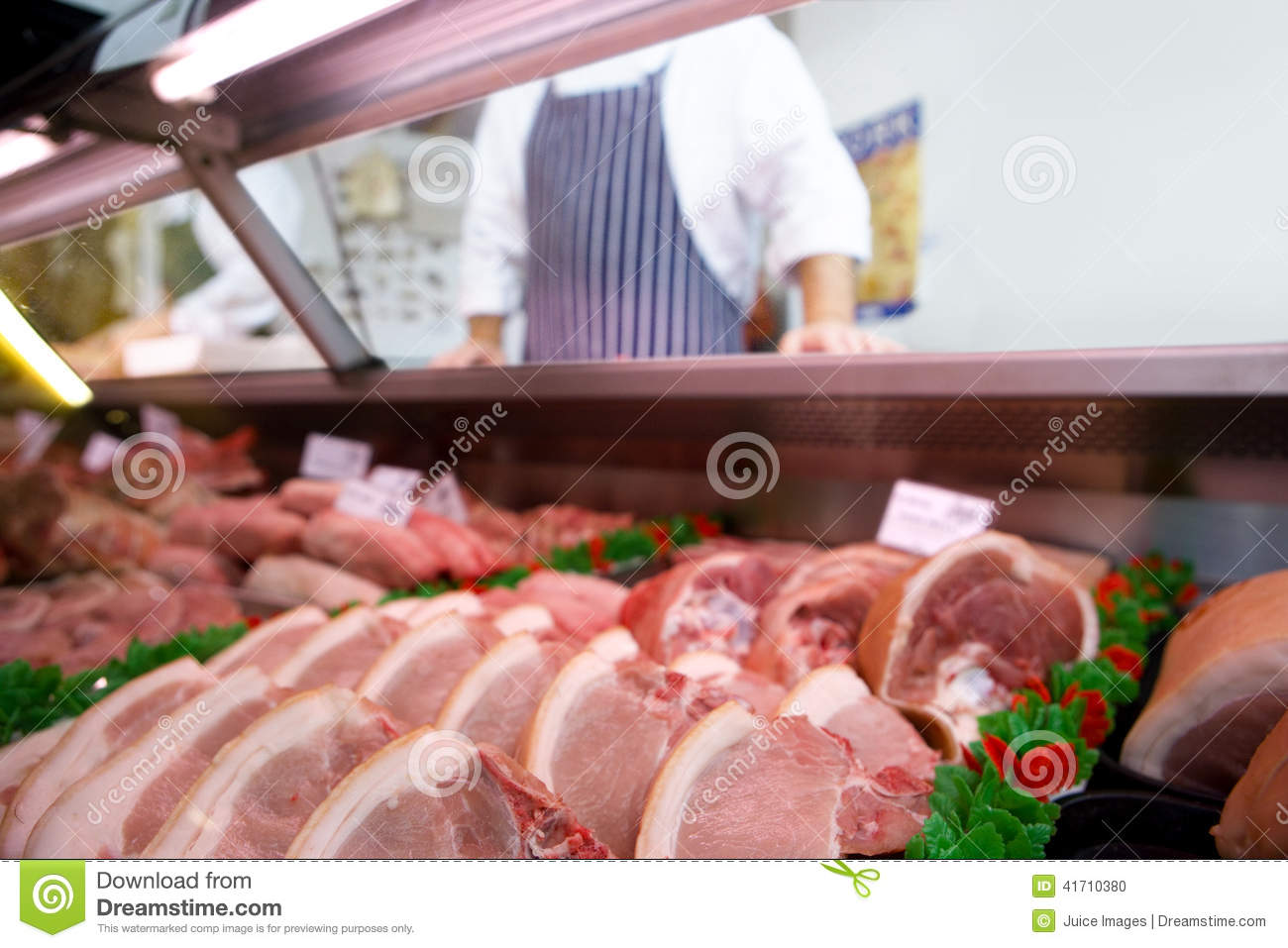 Chops in butcher`s shop, butcher in background, mid section