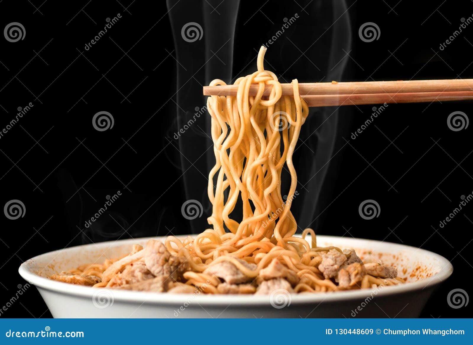 Chopsticks παίρνουν τα νόστιμα νουντλς με τον καπνό στο σκοτεινό υπόβαθρο Ramen στο άσπρο κύπελλο