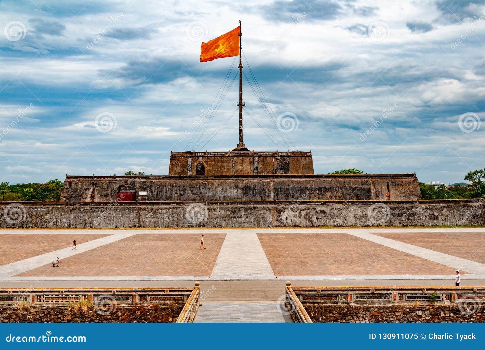 Chorągwiany wierza w odcieniu, Wietnam, z komunista flagą, dramatycznymi chmury i turyści w forground - symetryczny widok