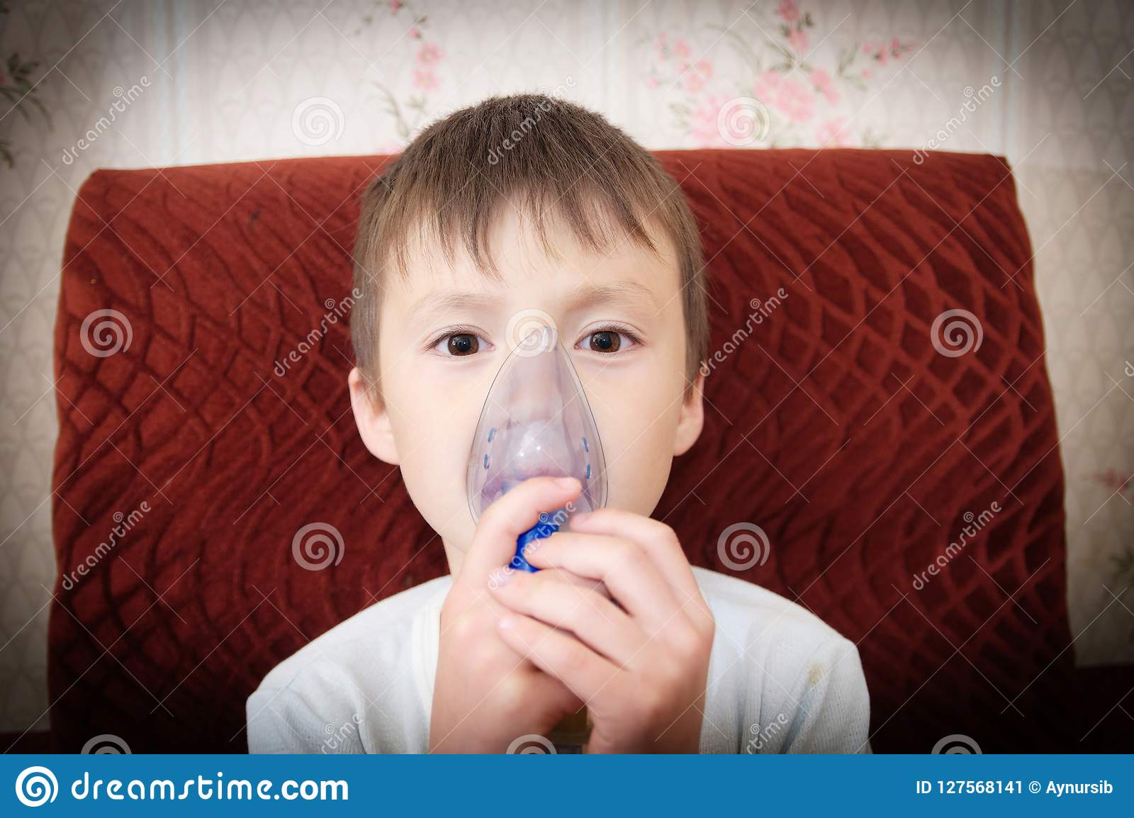 Chora chłopiec w nebulizer maskowej robi inhalaci, oddechowej procedurze zapaleniem płuc lub kasłaniu dla dziecka, inhalator