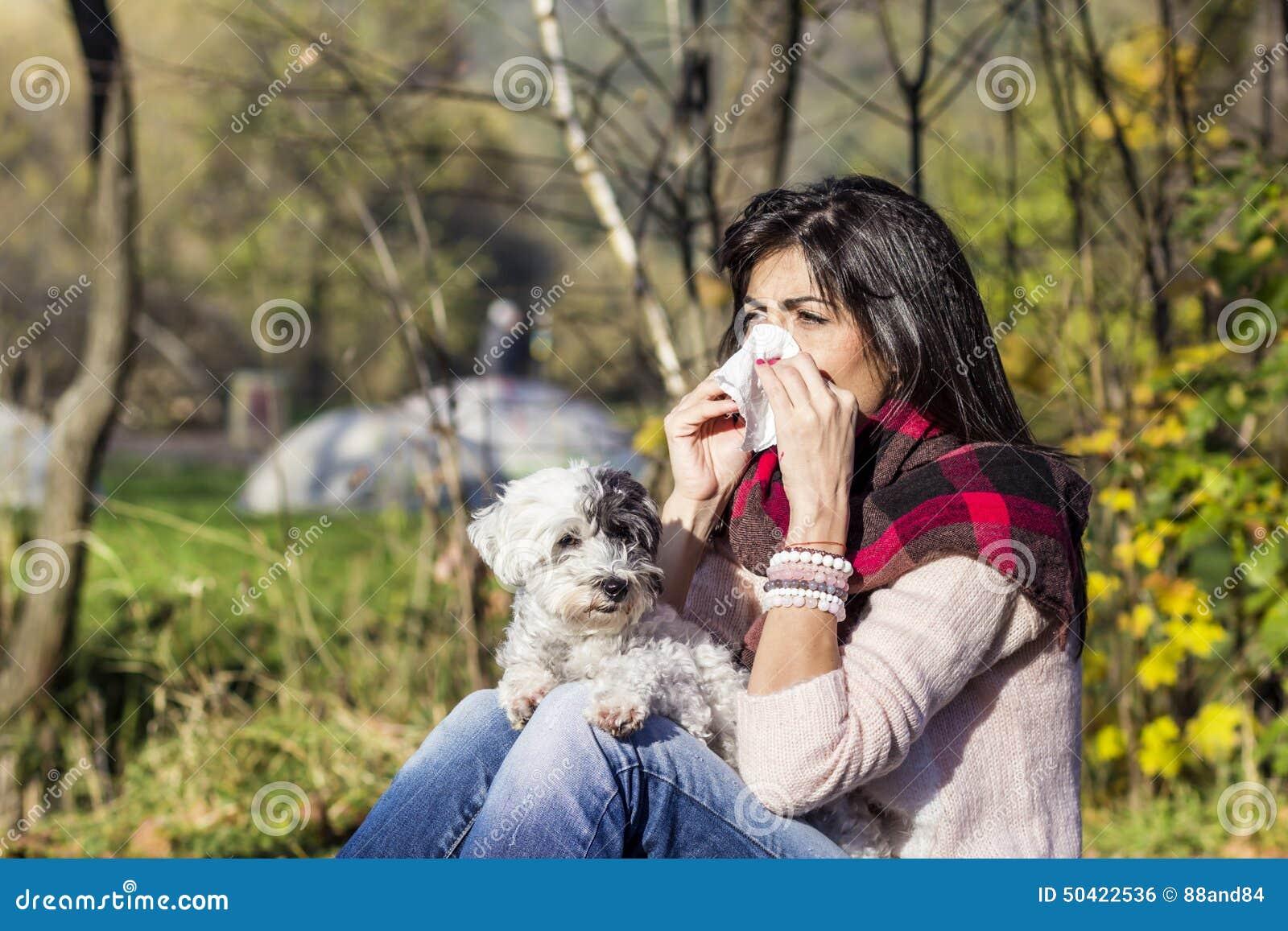 Chora kobieta relaksuje w jesień parku z jej psem