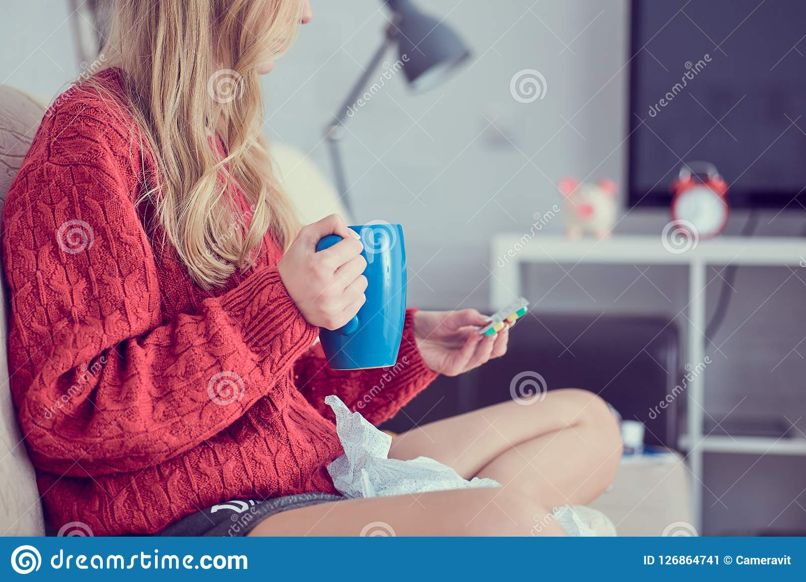 Chora młoda dziewczyna z pigułkami i filiżanka herbaciany obsiadanie na kanapie