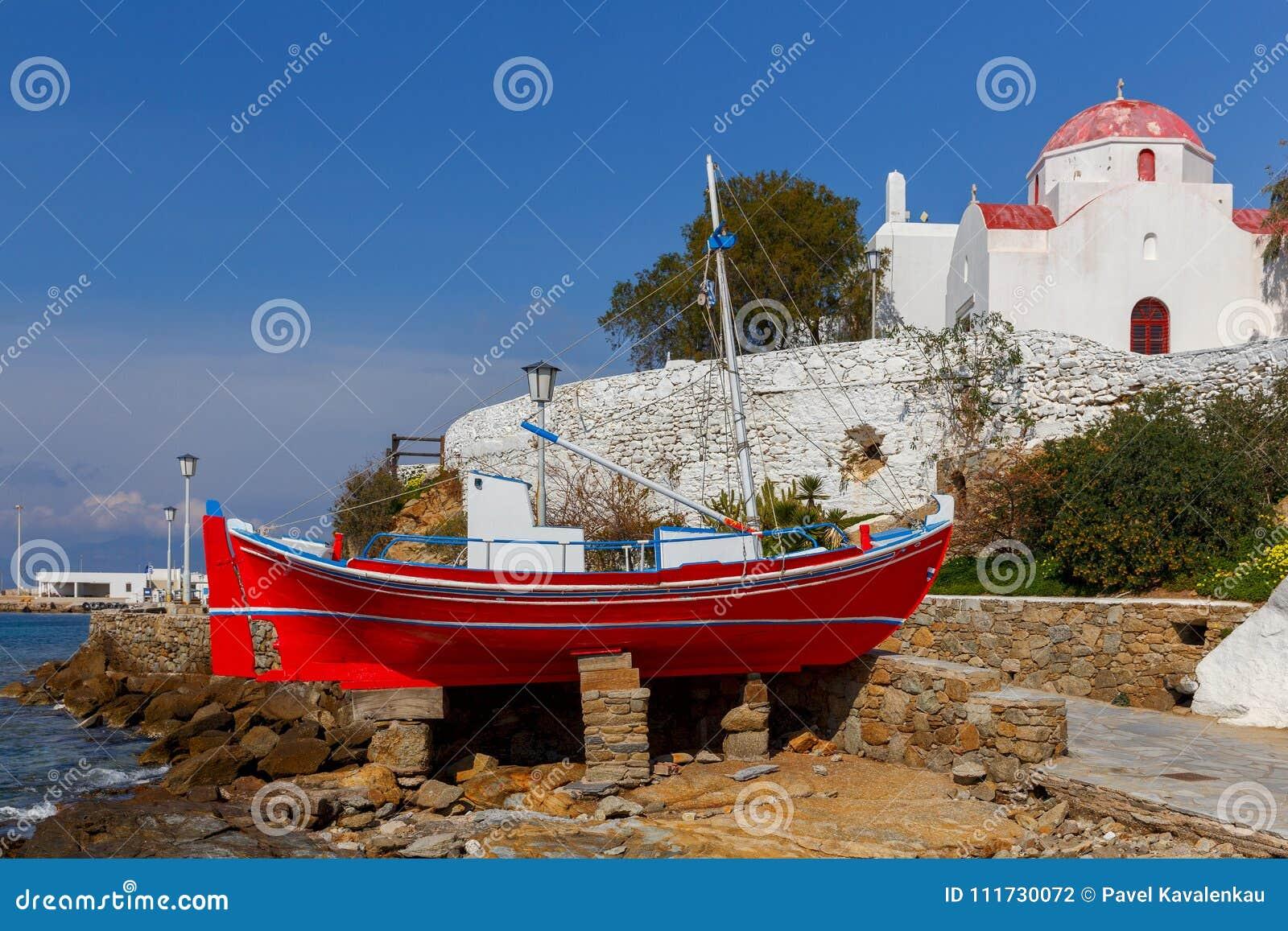 Chora Mykonos Красная рыбацкая лодка на береге