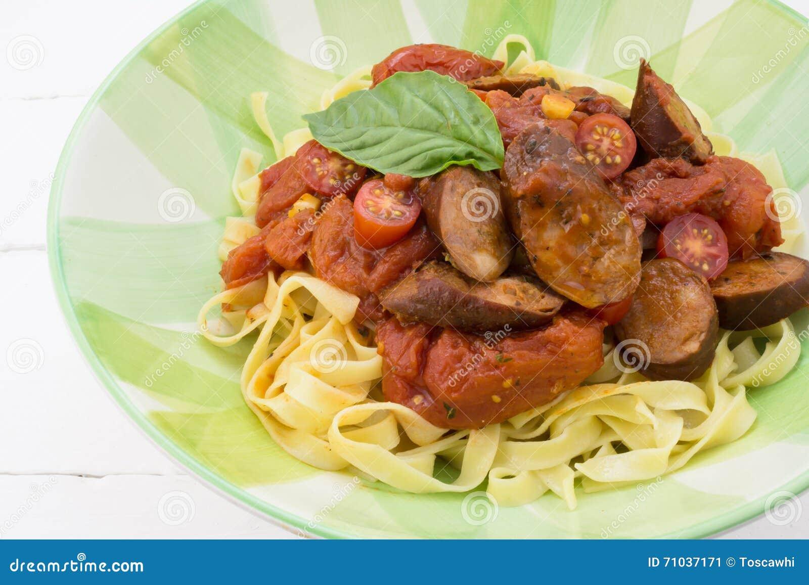 Chorizo kiełbasa i pomidoru makaronu posiłek z basilem w półkowym isolat