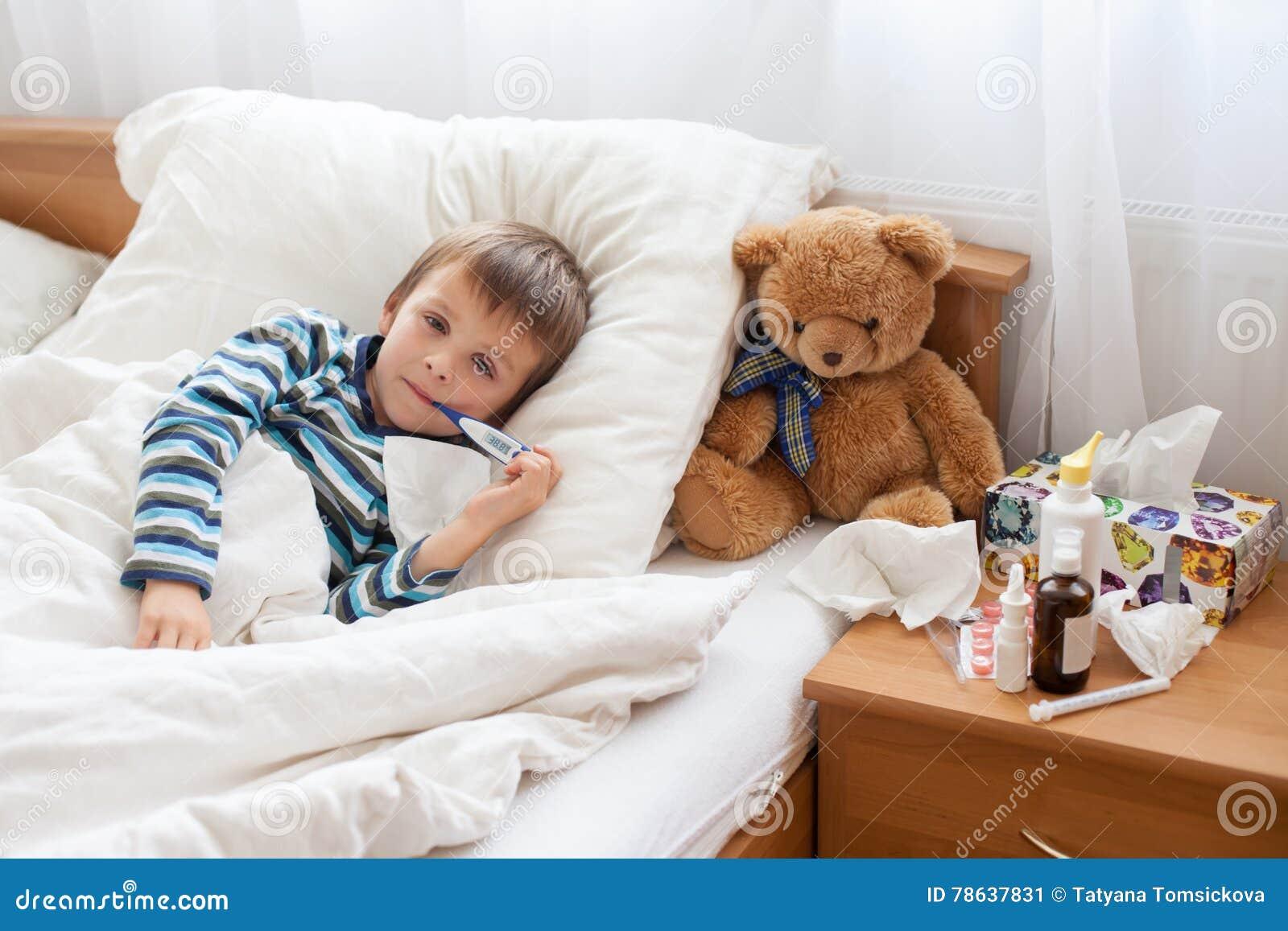 Chory dziecko chłopiec lying on the beach w łóżku z febrą, odpoczywa