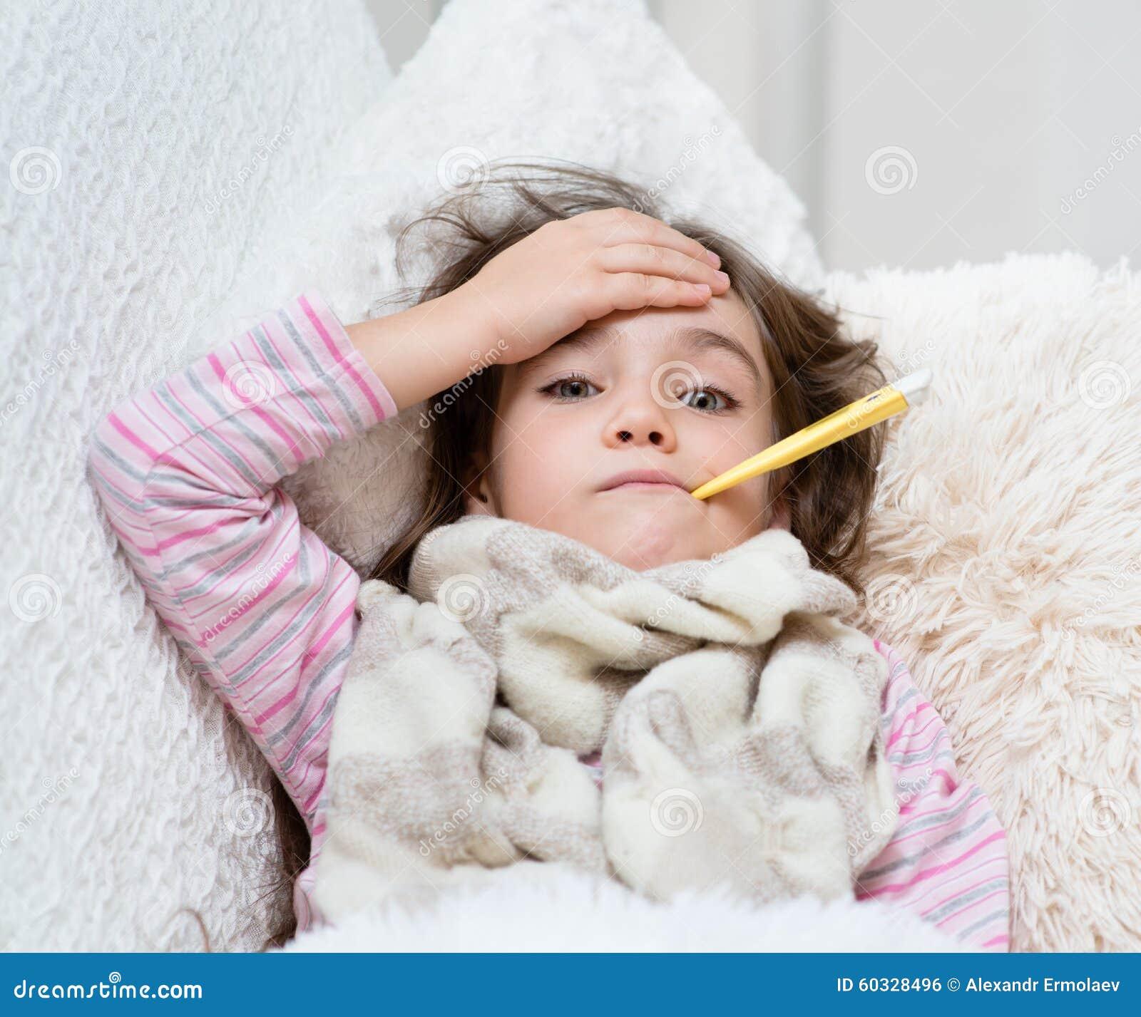 Chory dziewczyny lying on the beach w łóżku z termometrem w usta i dotyka jego czoło