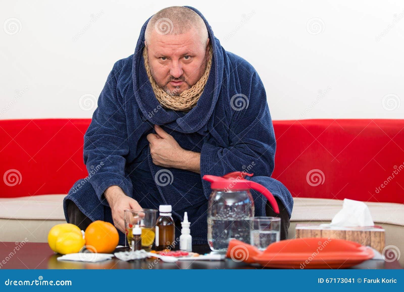 Chory mężczyzna jest ubranym piżamy cierpienia zimy i zimna grypowego wirusa ma medycynę
