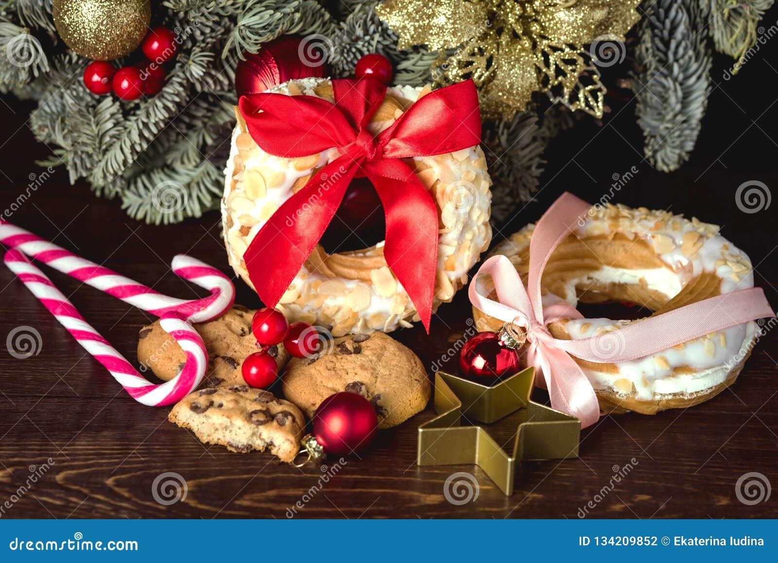Choux pastelaria e cookies dos anéis do sopro de creme em doces festivos Cane Christmas Wreath do conceito do alimento do Natal d