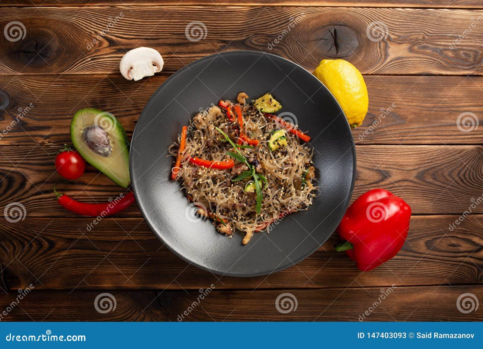 Chow νουντλς θαλασσινών στο μαύρο πιάτο στο ξύλινο υπόβαθρο