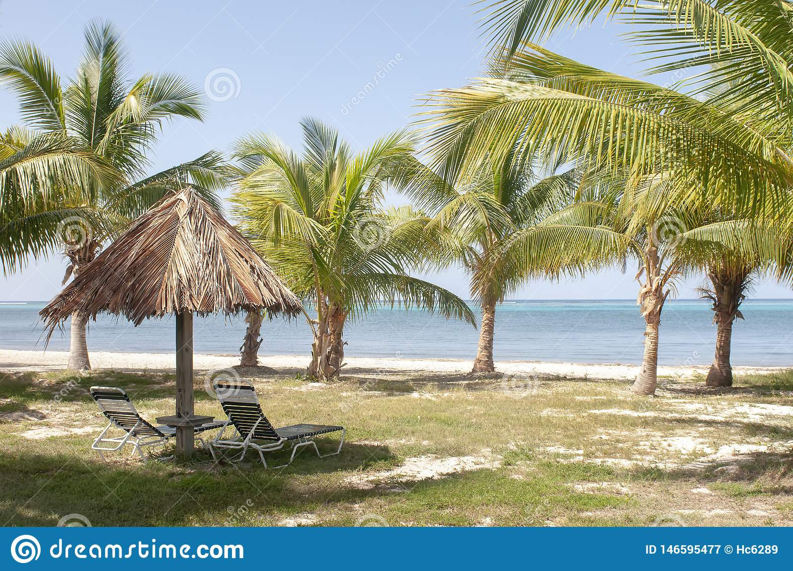 Choza con las sillas y las palmeras en paisaje de la playa con aguas azules hermosas en la isla