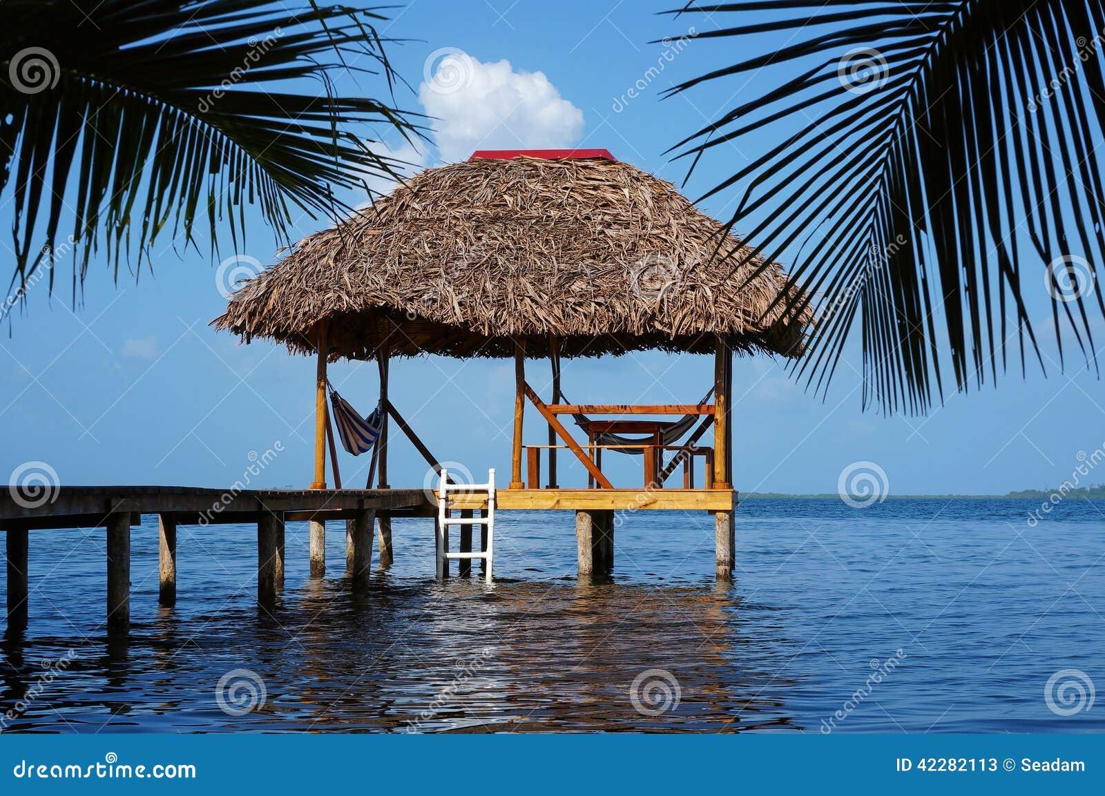 Choza de palapa con el tejado cubierto con paja sobre el for Bungalows dentro del mar