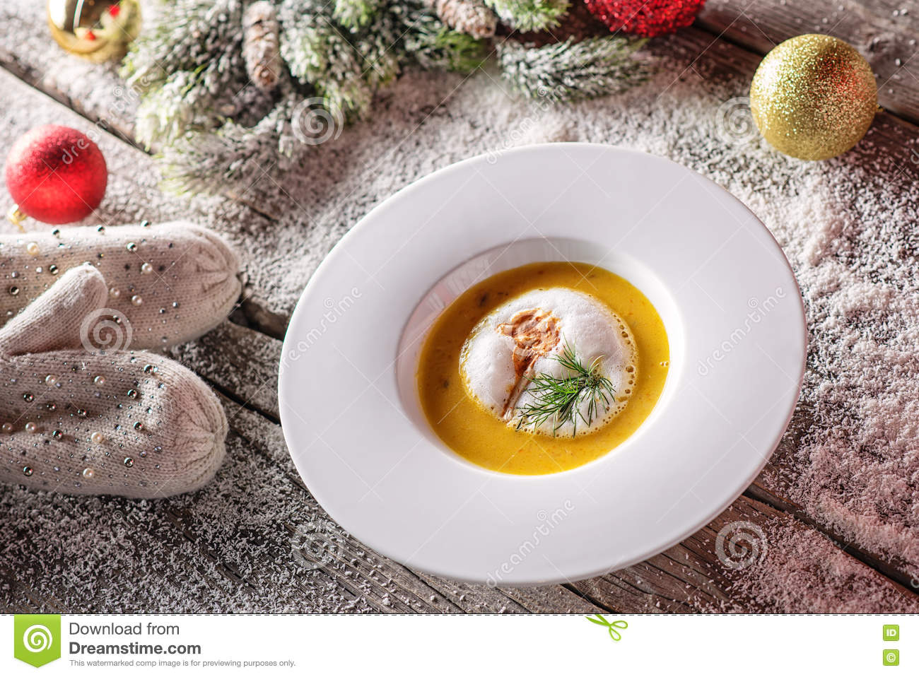 Chrismas fish soup in white plate with christmas decorations, modern gastronomy