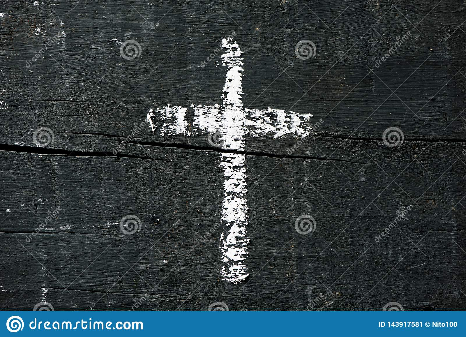 Christian cross on a dark gray wooden surface