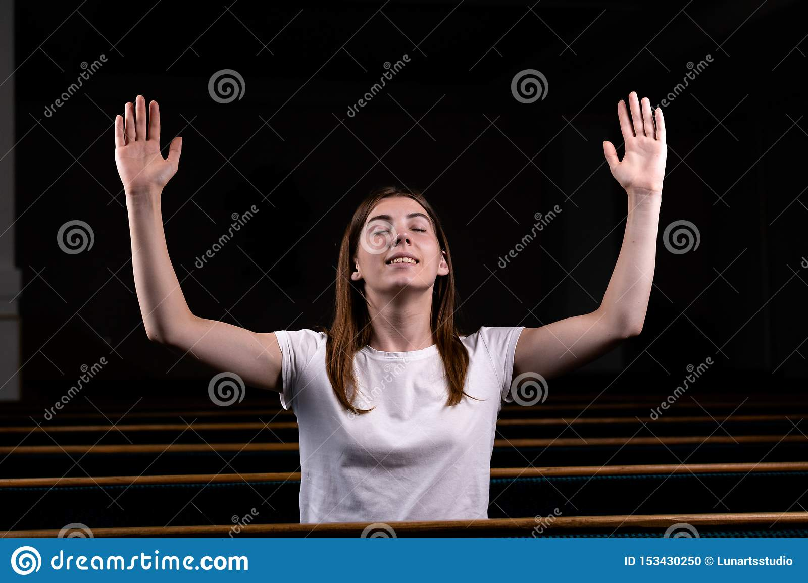 A Christian girl in white shirt is sits with his hands up and face and praying with humble heart in the church