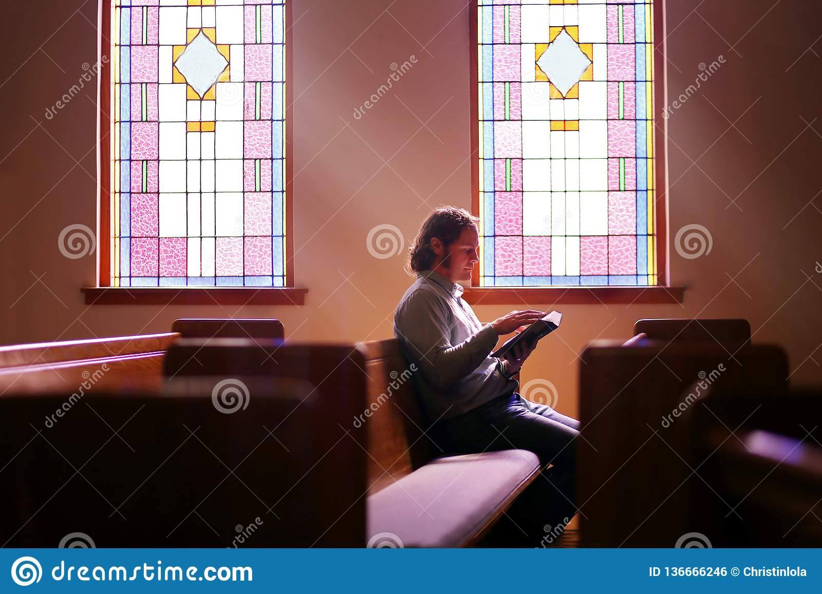 Christian Man Sitting Alone in Donkere Lege Kerkbank door Helder Gebrandschilderd glasvenster