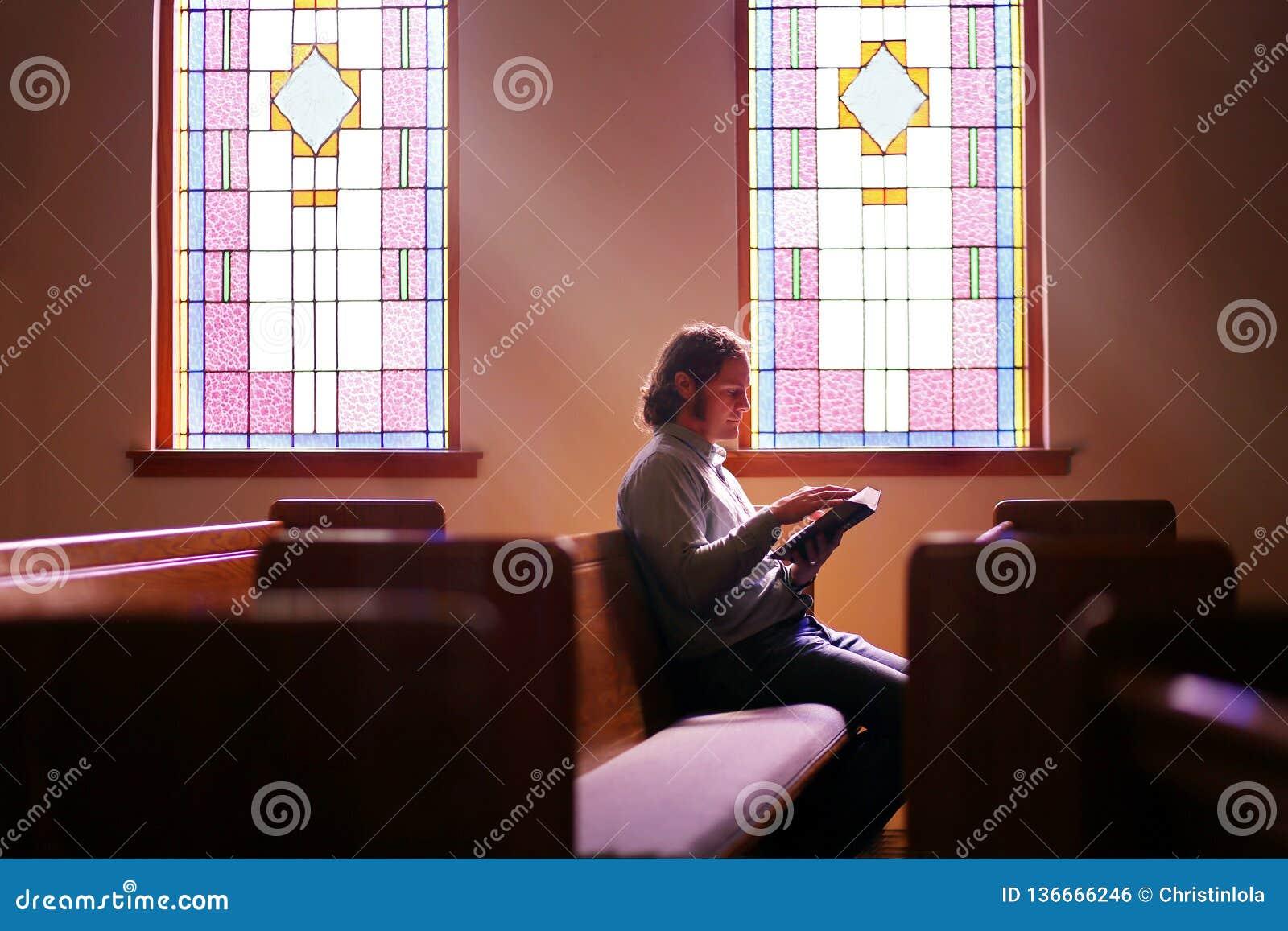 Christian Man Sitting Alone en banco vacío oscuro de la iglesia por el vitral brillante