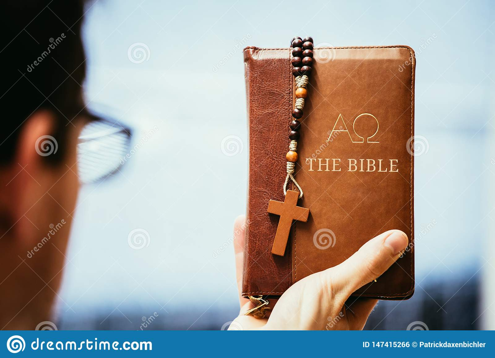 Christian preacher: Young man is holding the bible, praying