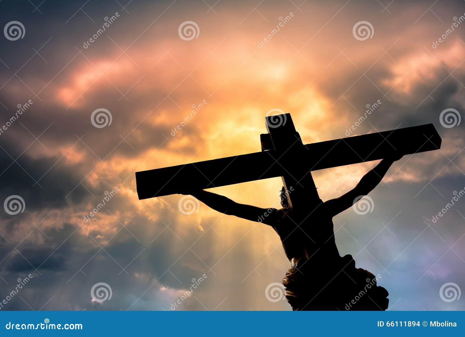 Christliches Kreuz mit Jesus Christ-Statue über stürmischen Wolken