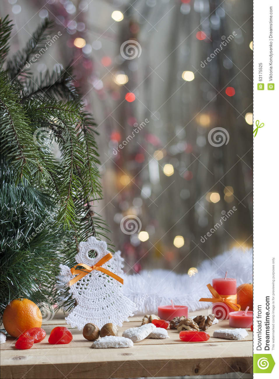Christmas angel in tree and red candles on colorful