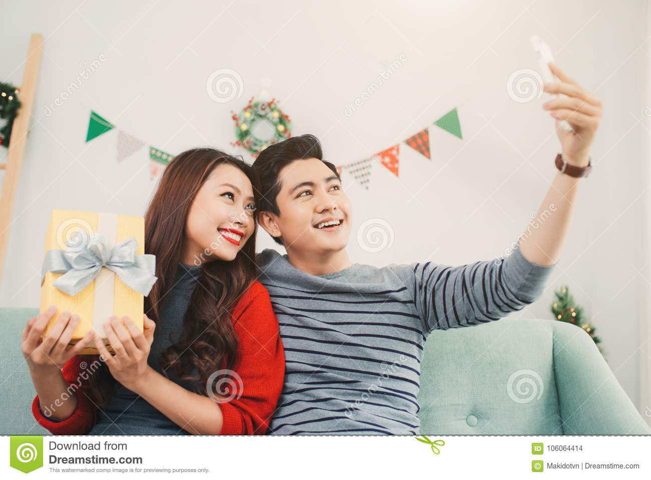 Christmas Asian Couple. A Handsome Man Giving Her ...