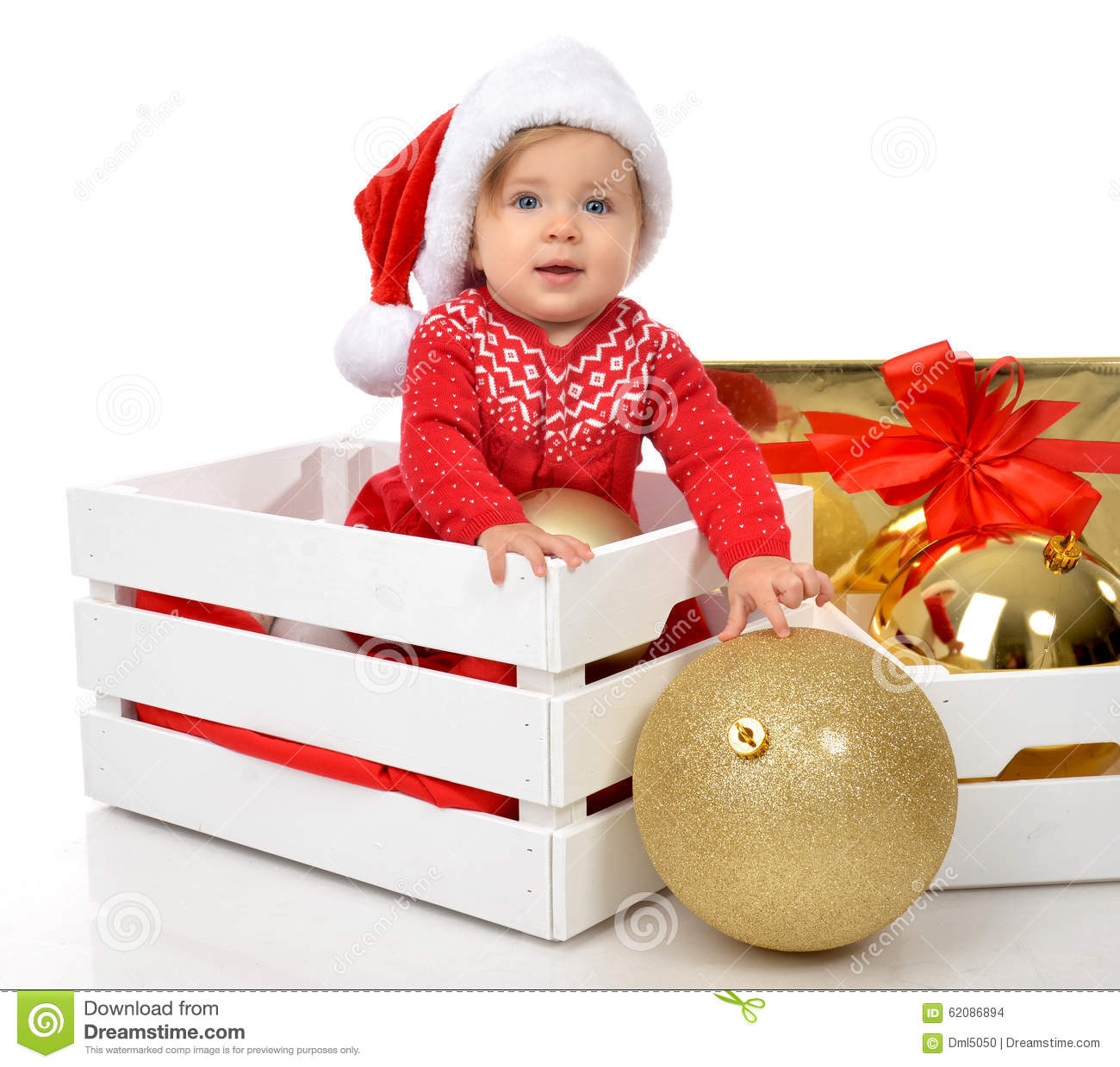Christmas baby child in santa hat hold gold ball for Decoration on a present