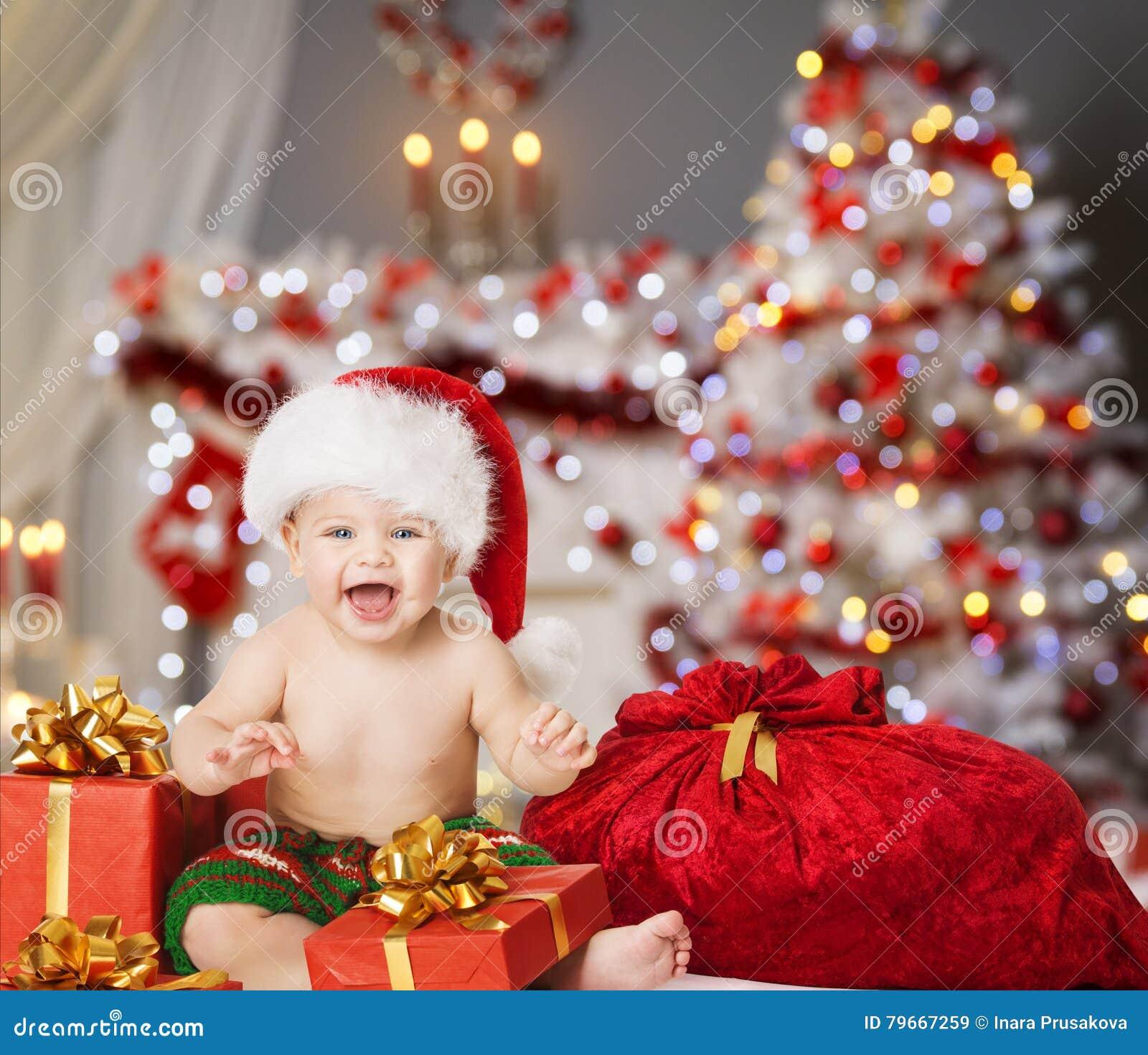 Christmas baby in santa hat kid boy in xmas interior present gift box and bag