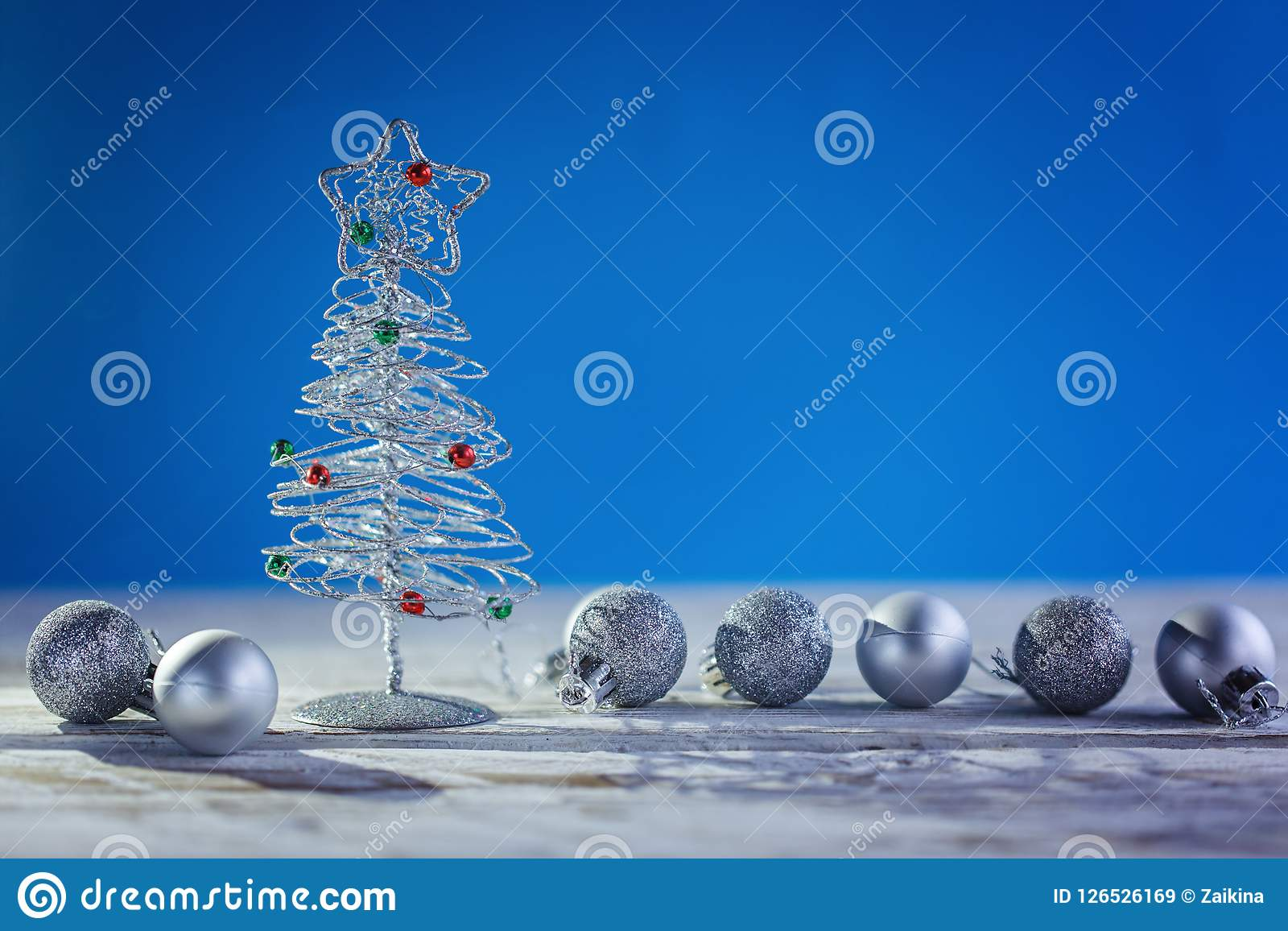 Christmas background with decorative silver Christmas tree and ball on blue background.
