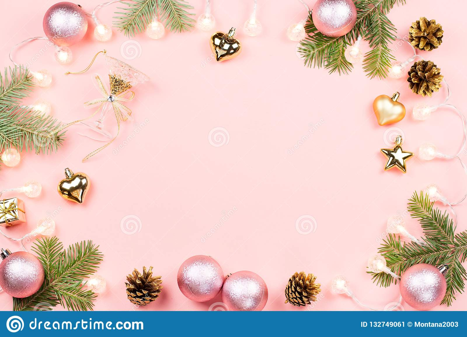 Christmas background with fir branches, lights, pink decorations on pink