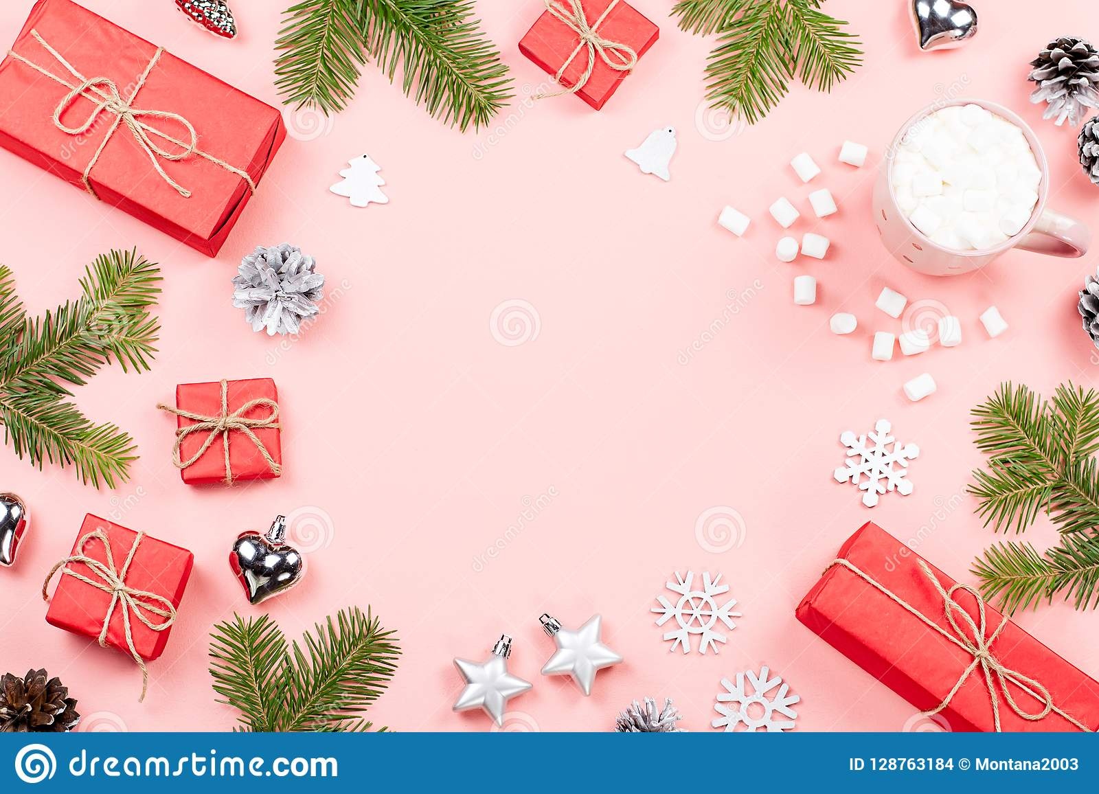 Christmas background with fir branches, lights, red giftboxes, pink decorations, hot drink with marshmallows on pink