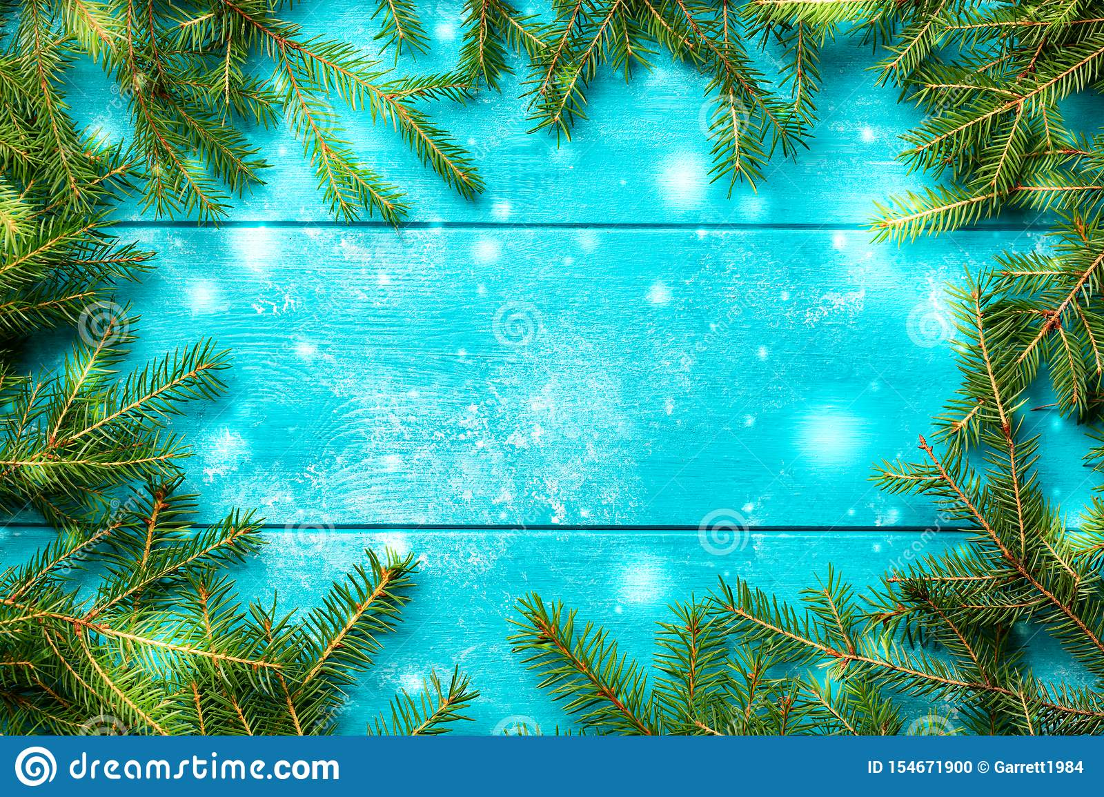 Christmas background. Christmas fir tree branches with snow on blue rustic wooden board with copy space