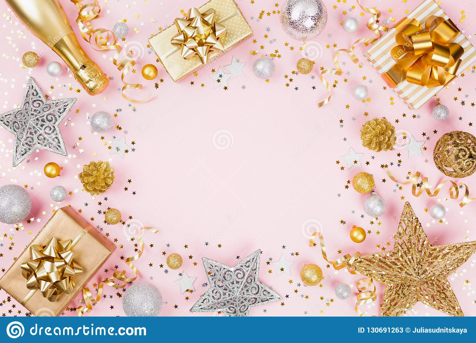 Christmas background with gift or present box, champagne, confetti and holiday decorations on pink pastel table top view. Flat lay
