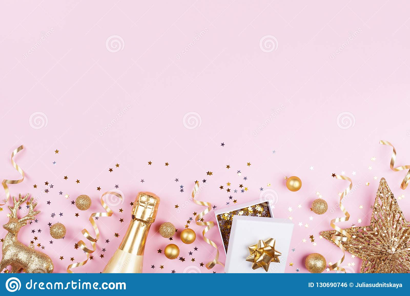 Christmas background with golden gift or present box, champagne and holiday decorations on pink pastel table top view. Flat lay.