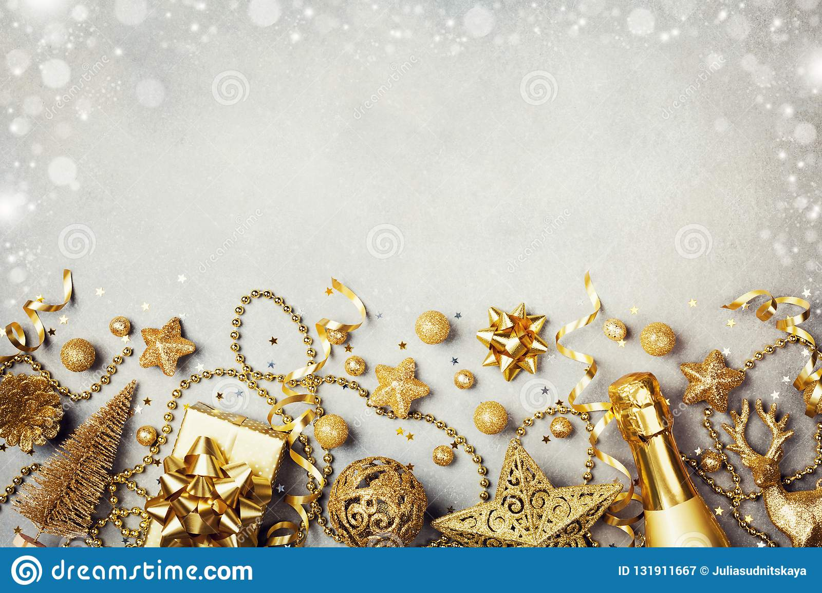 Christmas background with golden gift or present box, champagne and holiday decorations top view. Greeting card. Flat lay style