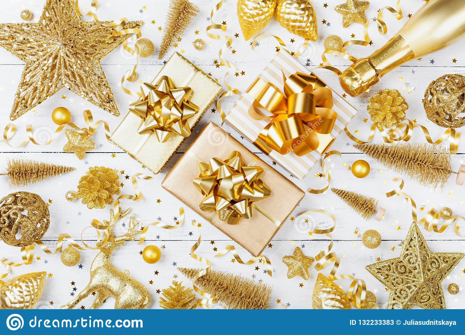 Christmas background with golden gift or present box, champagne and holiday decorations on white table top view. Greeting card.