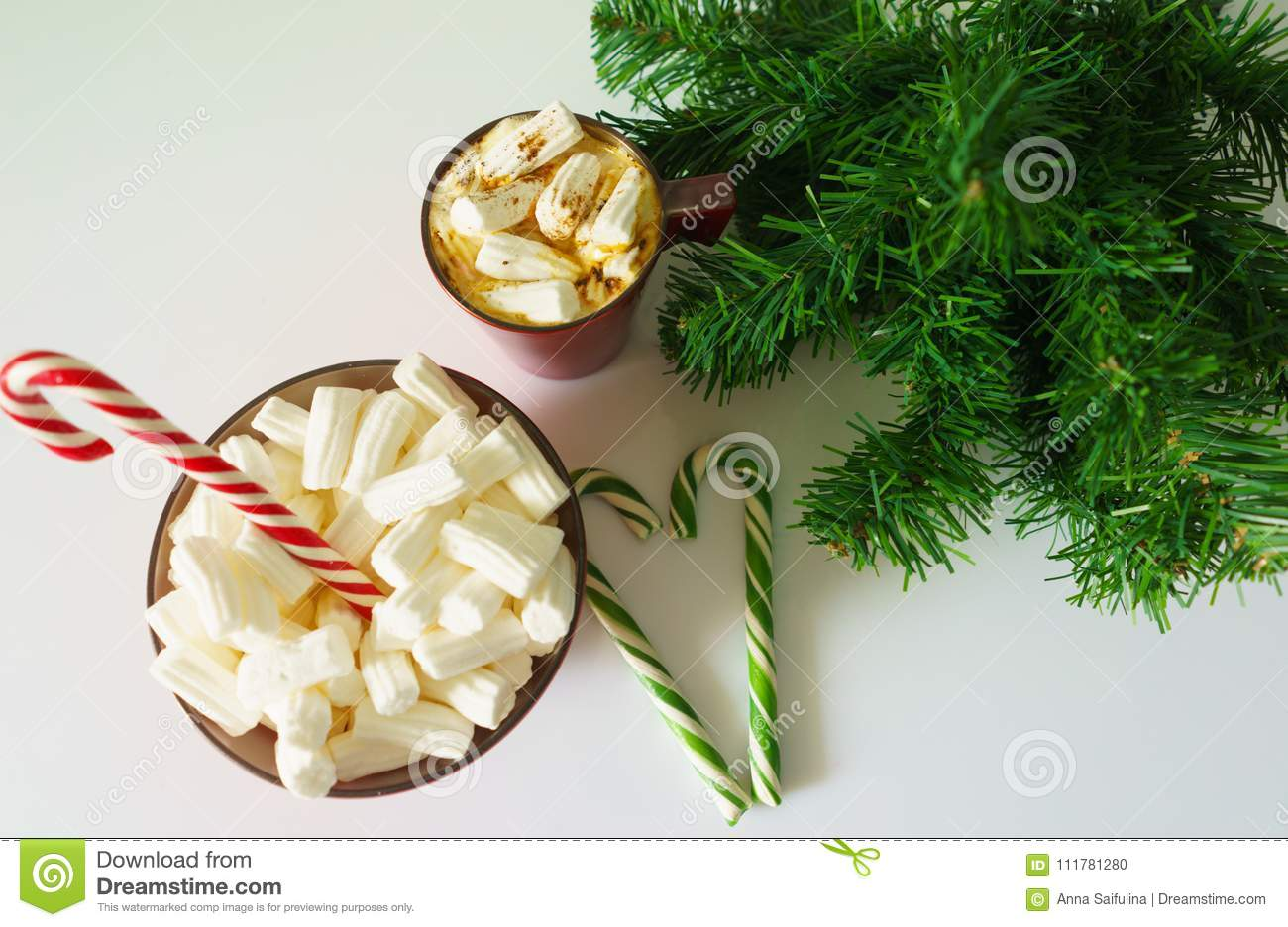 Christmas background, greeting card with a Cup of coffee or chocolate with marshmallows,candy canes, a red plate and tree branches