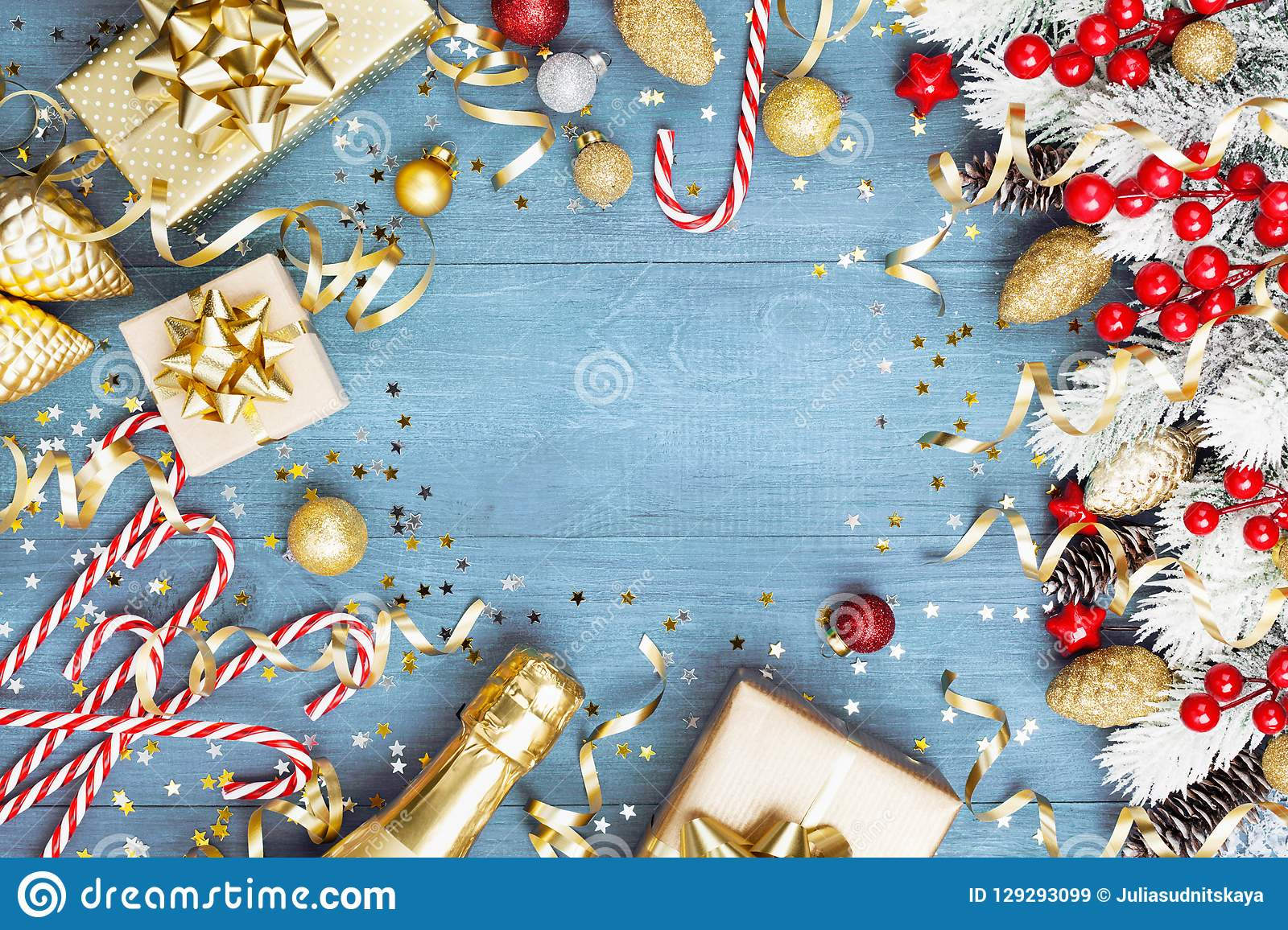 Christmas background with snowy fir tree, gift or present box, champagne and holiday decorations on blue wooden table top view.