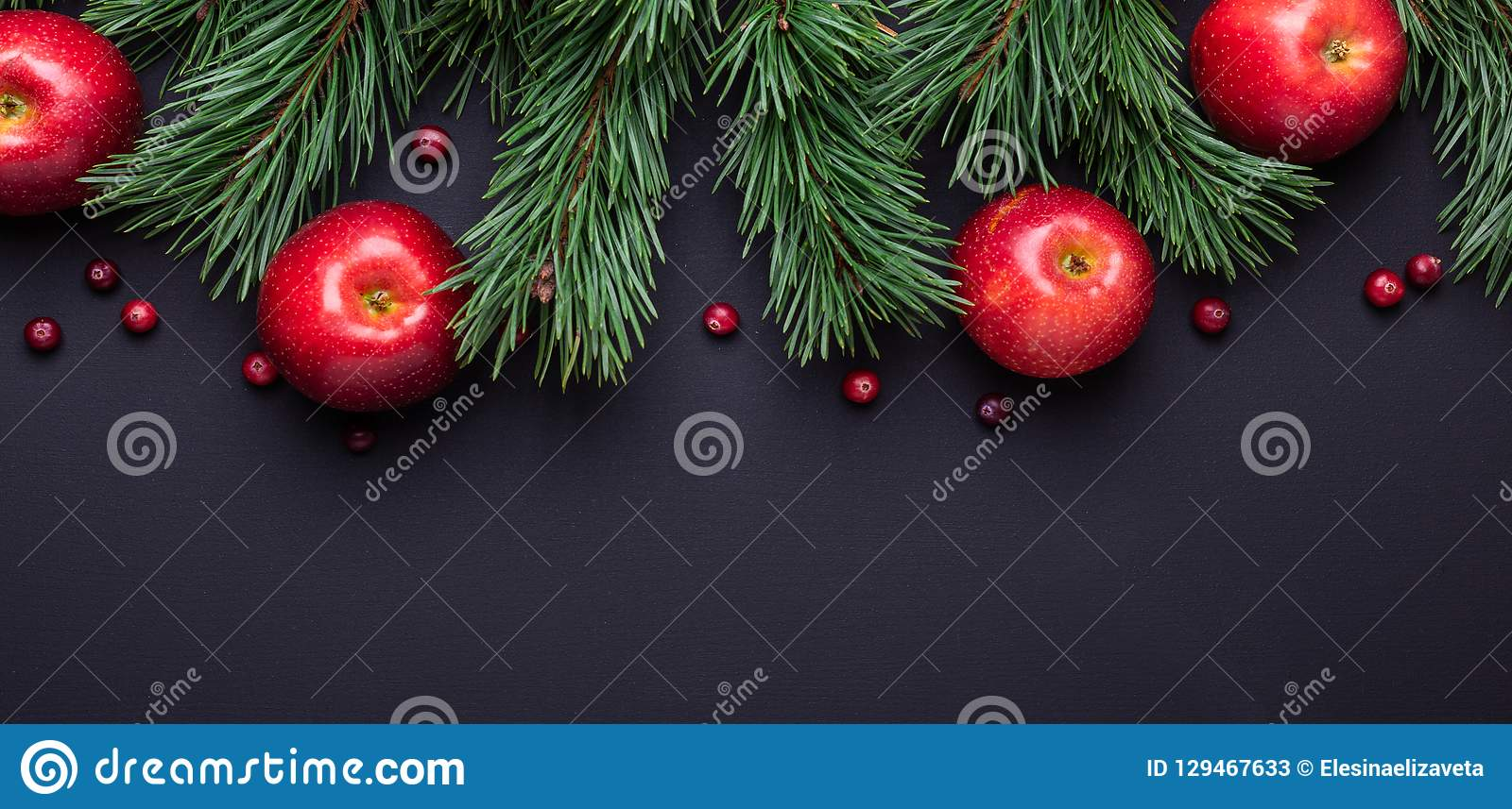 Christmas background with tree branches, red apples and cranberries. Dark wooden table
