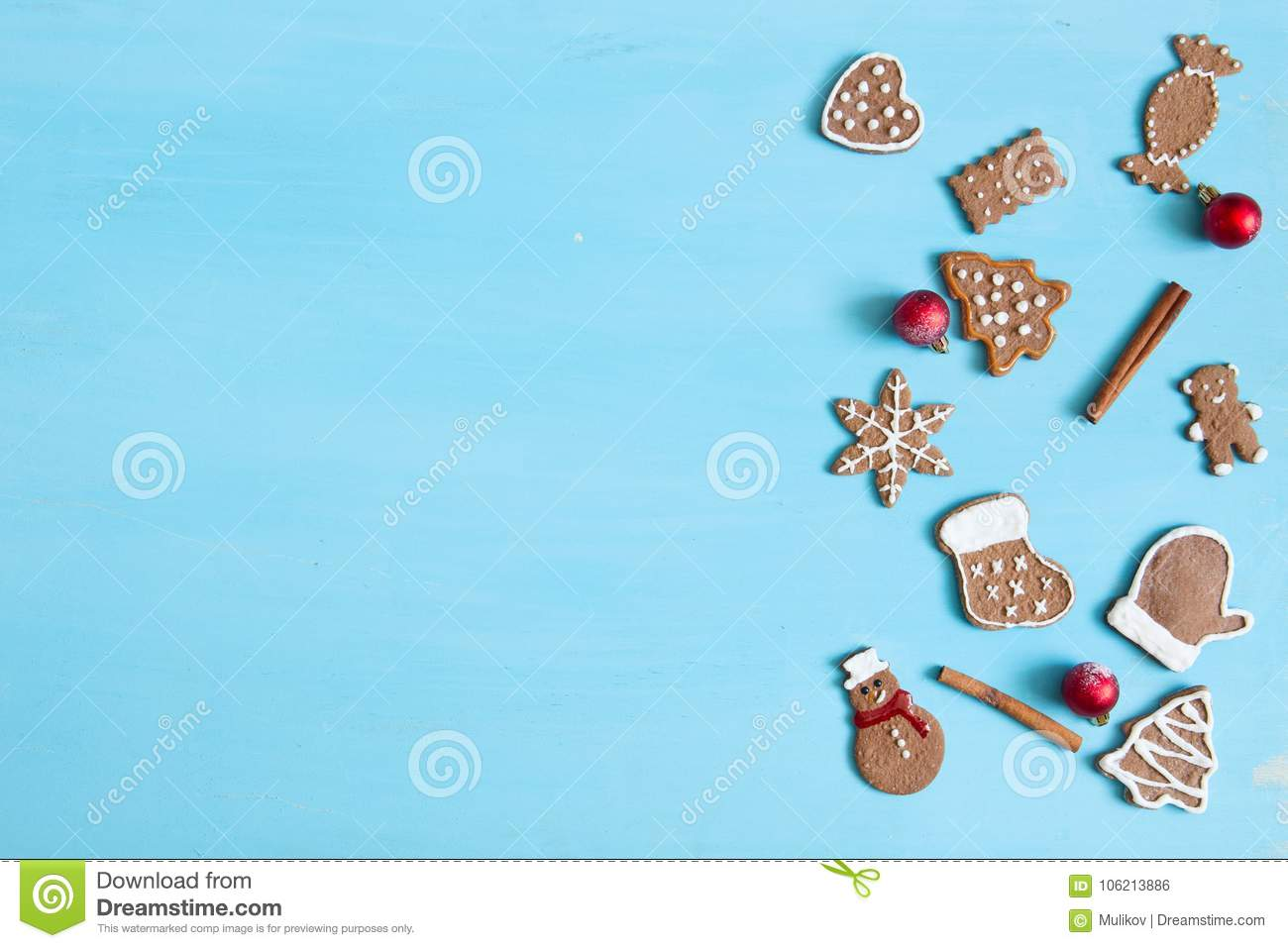 Christmas baking background. Christmas gingerbread cookies and spices on blue table. Top view