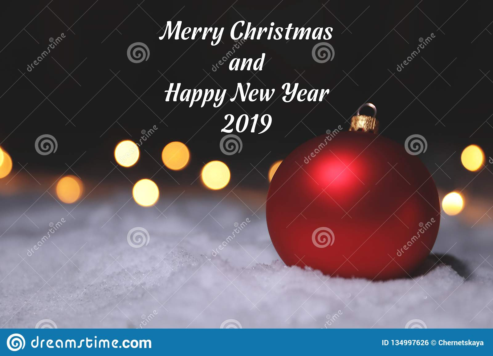 Christmas ball on snow and greeting message against blurred background.