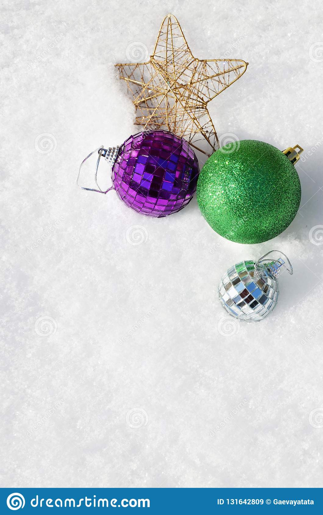 Christmas balls and a star in the snow, top view.