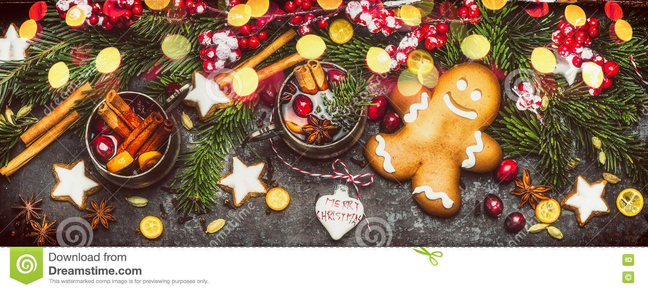 Christmas banner with Gingerbread Man, Cookies, mulled wine ,holiday decorations , fir branches and festive bokeh lighting on dark