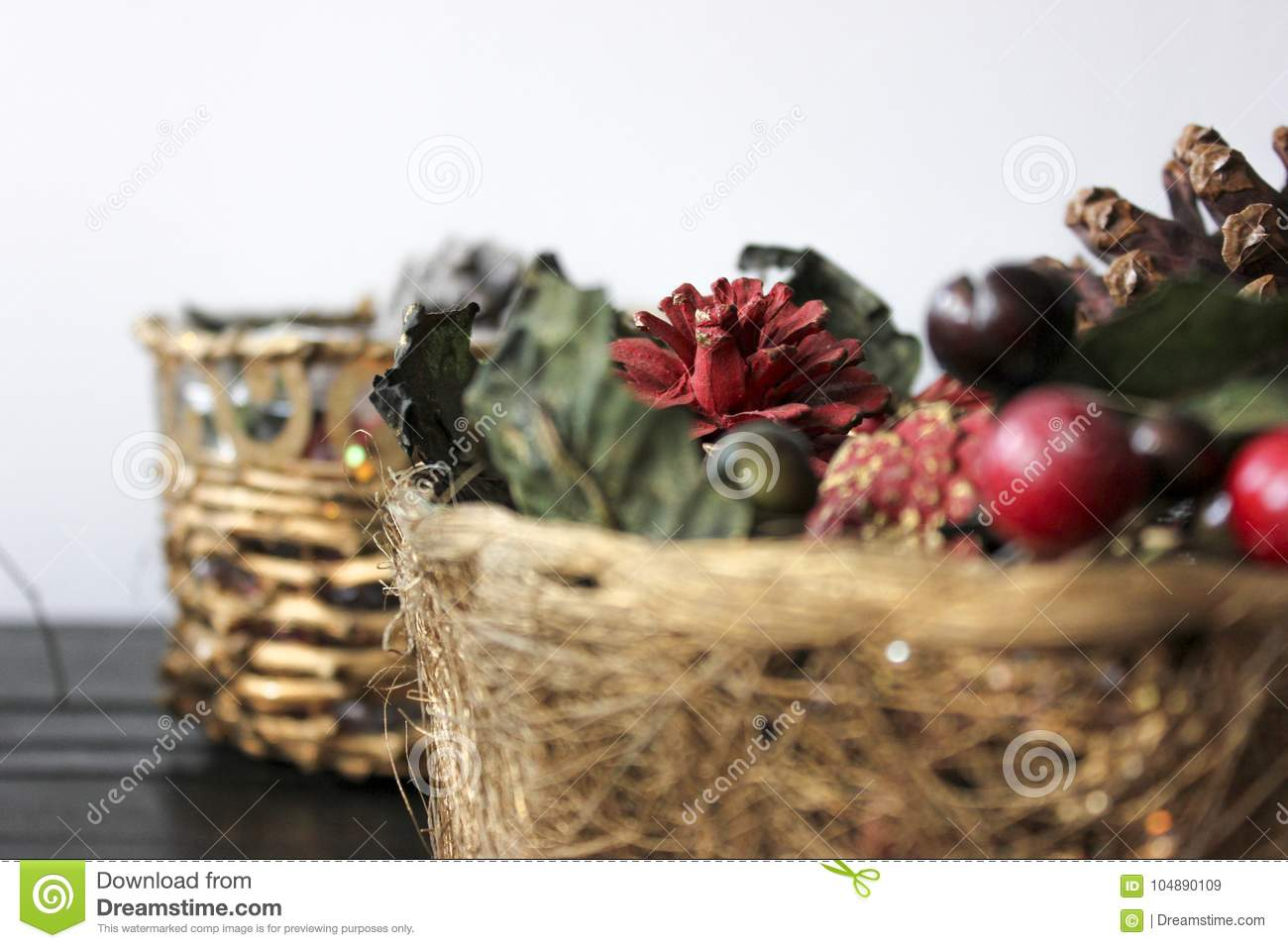 a christmas basket filled with cherries pines and green and red decorations
